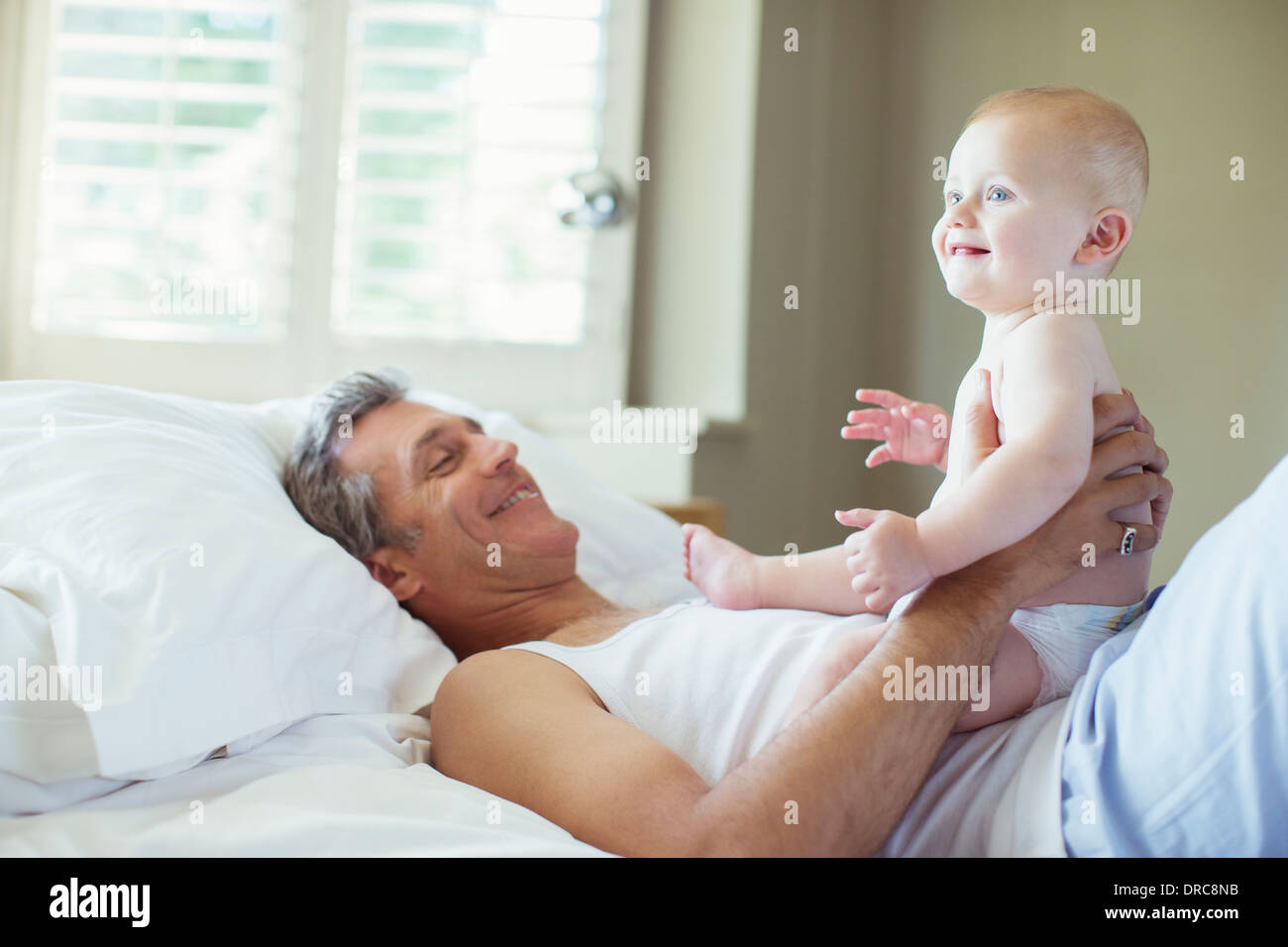 Father playing with baby on bed - Stock Image