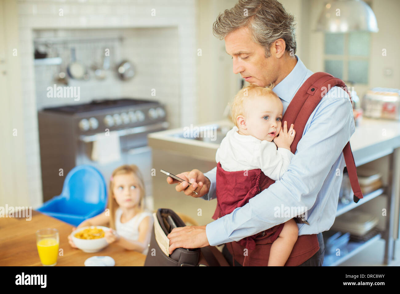 Father with baby packing bag for work - Stock Image