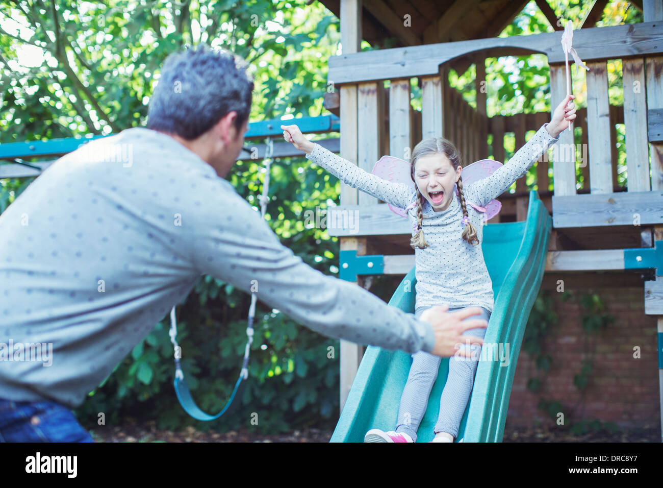 Father catching daughter on slide - Stock Image