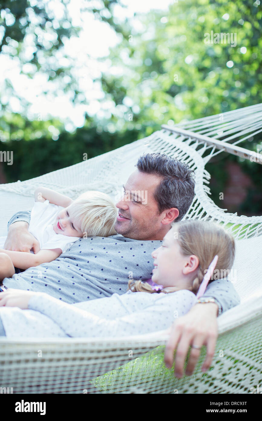 Father and children relaxing in hammock - Stock Image
