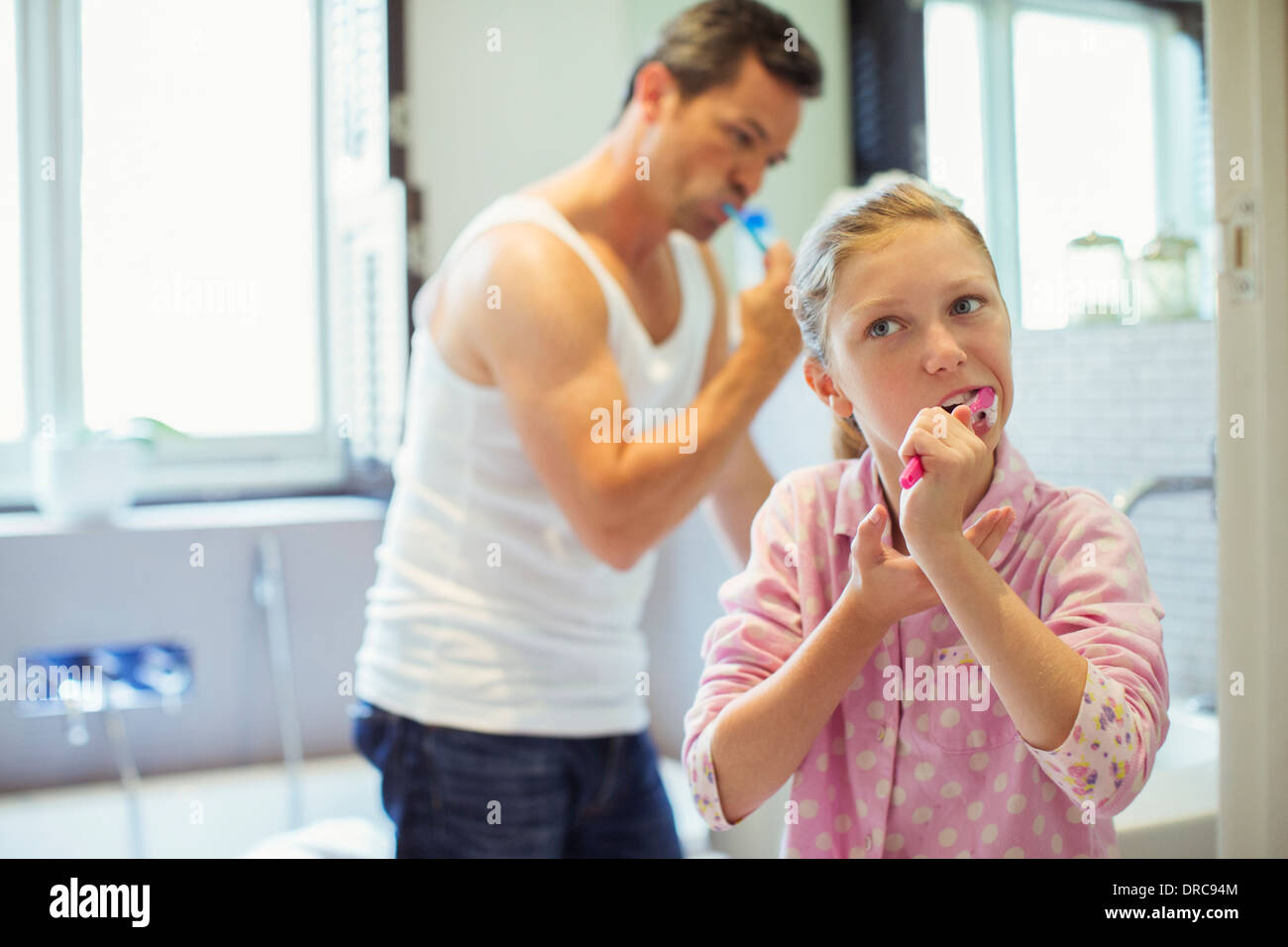 Father and daughter brushing teeth in bathroom - Stock Image