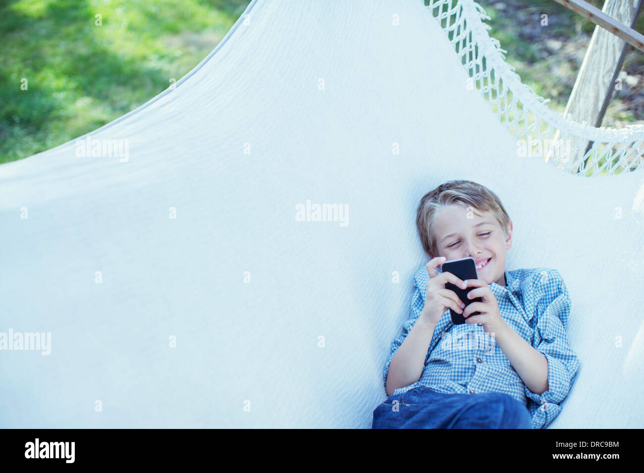 Boy using cell phone in hammock - Stock Image