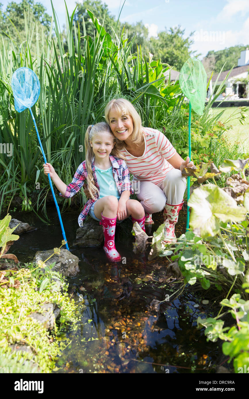 Woman and granddaughter fishing in pond - Stock Image