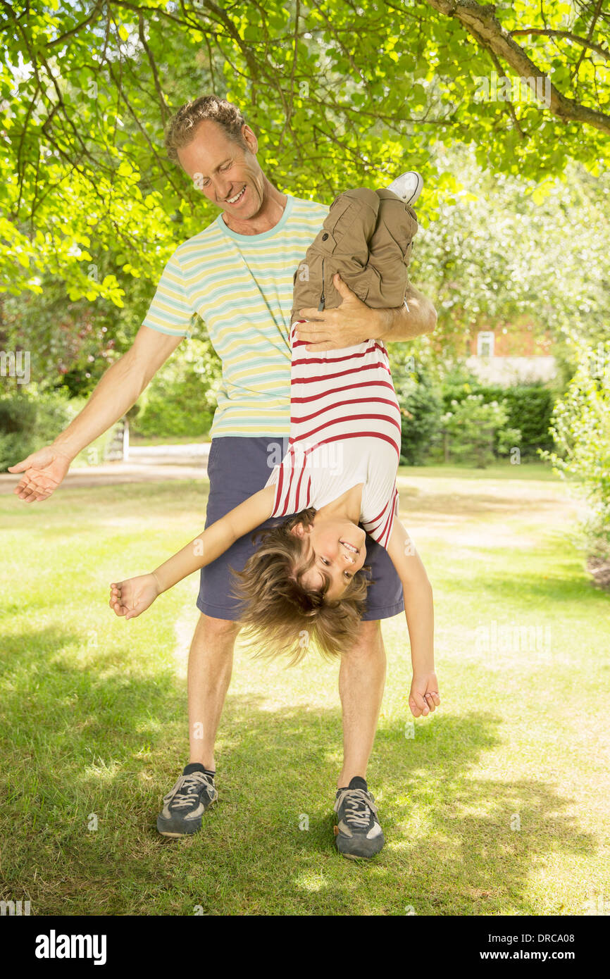 Father holding son upside-down in backyard Stock Photo