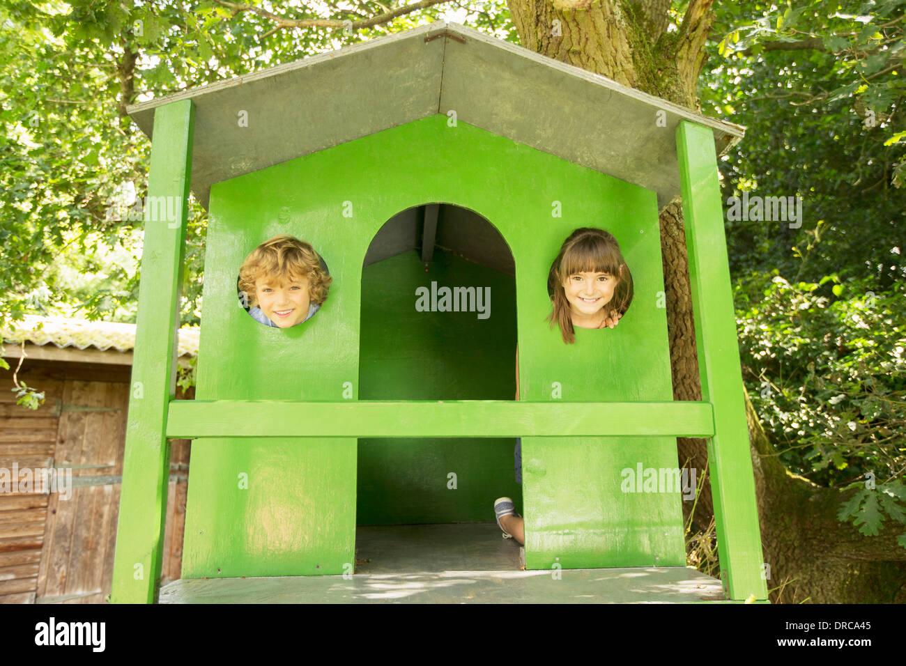 Children peeking through windows of treehouse - Stock Image