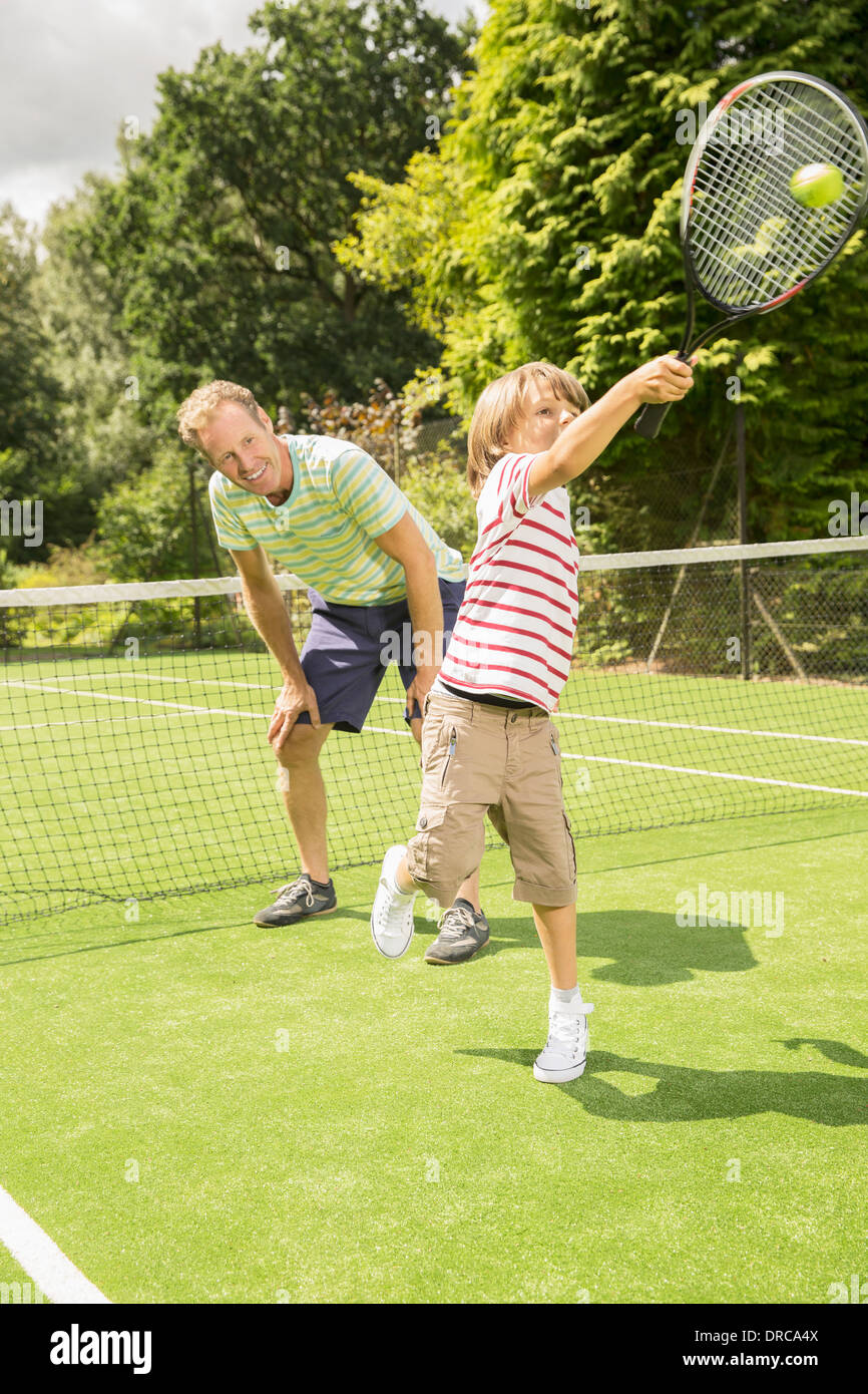 Father and son playing tennis on grass court - Stock Image