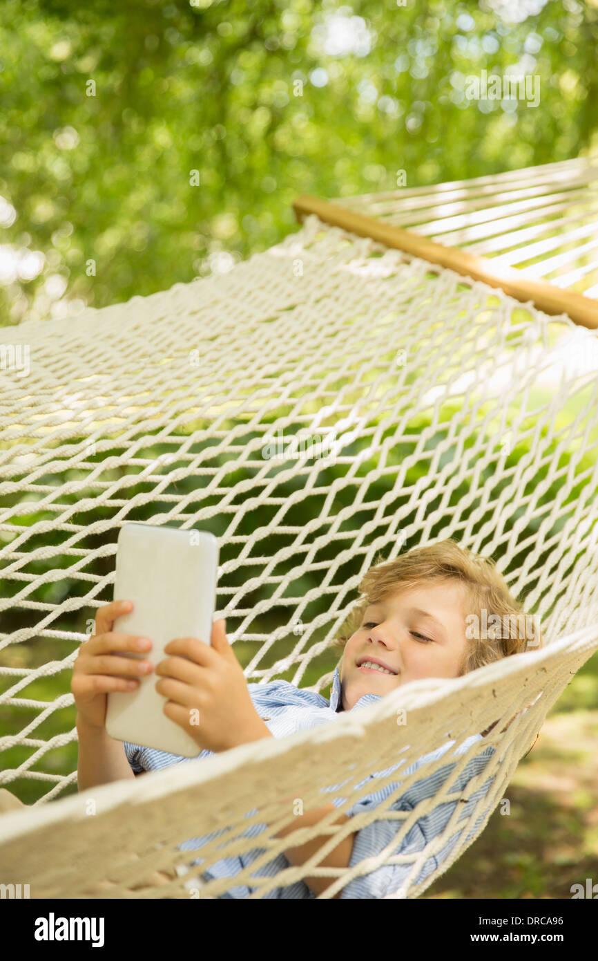 Boy using digital tablet in hammock - Stock Image