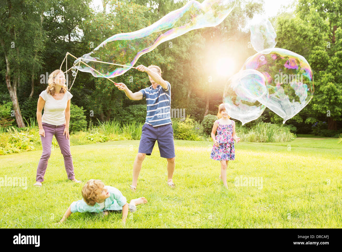Family playing with large bubbles in backyard Stock Photo