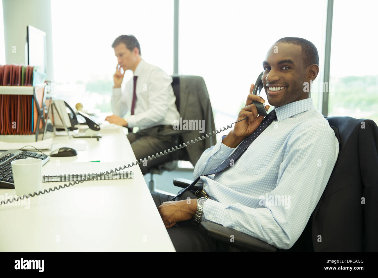 Businessman talking on telephone in office - Stock Image