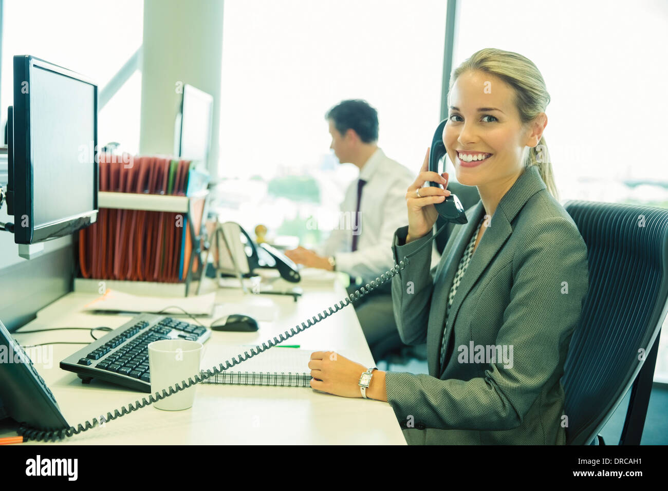 Businesswoman talking on telephone in office - Stock Image