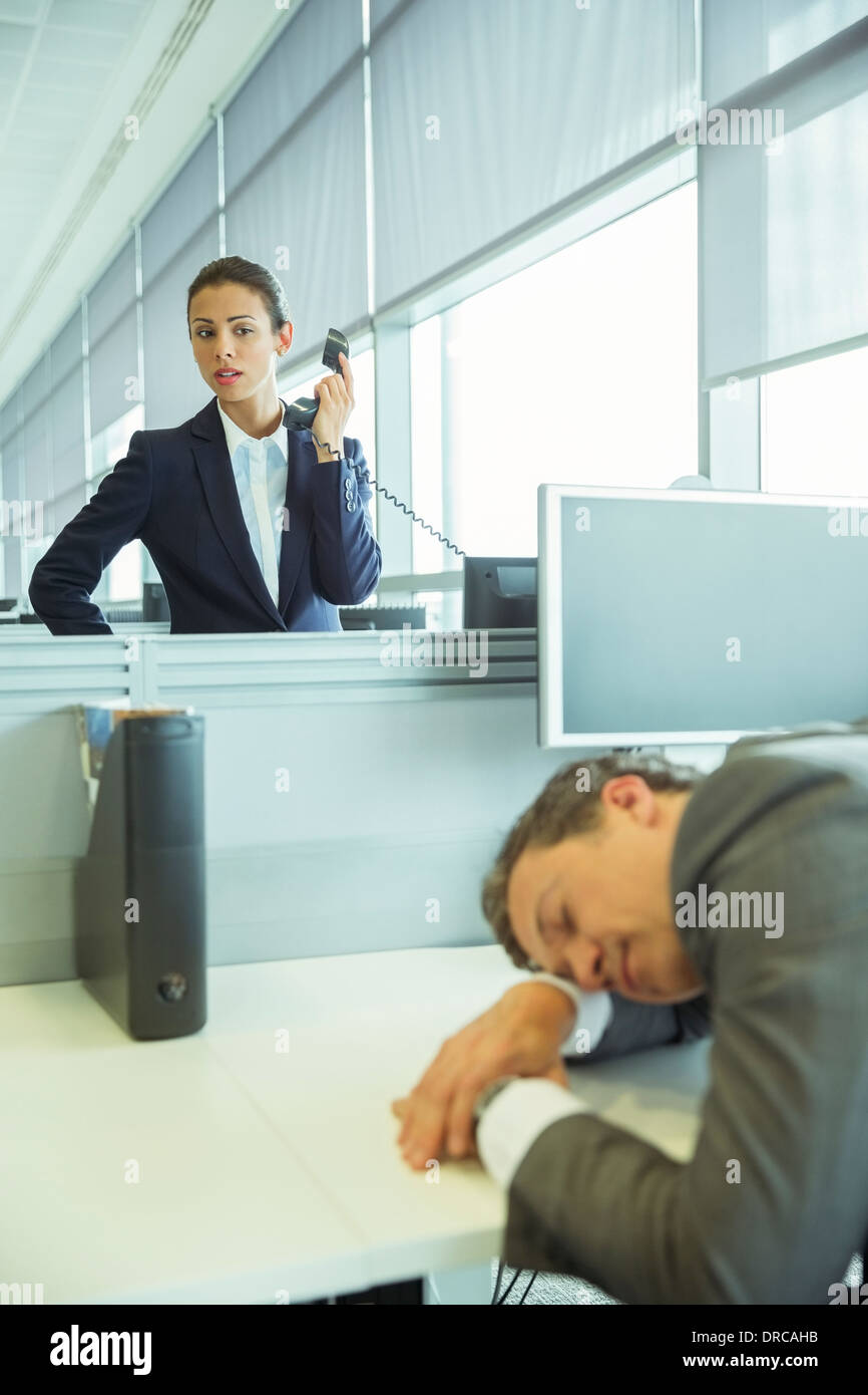 Businesswoman watching sleeping businessman in office - Stock Image