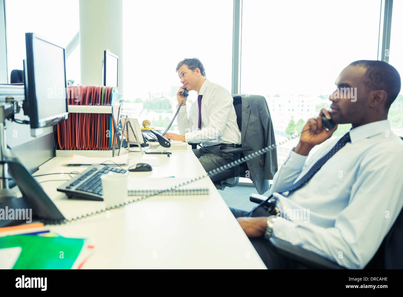 Businessmen talking on telephones in office - Stock Image