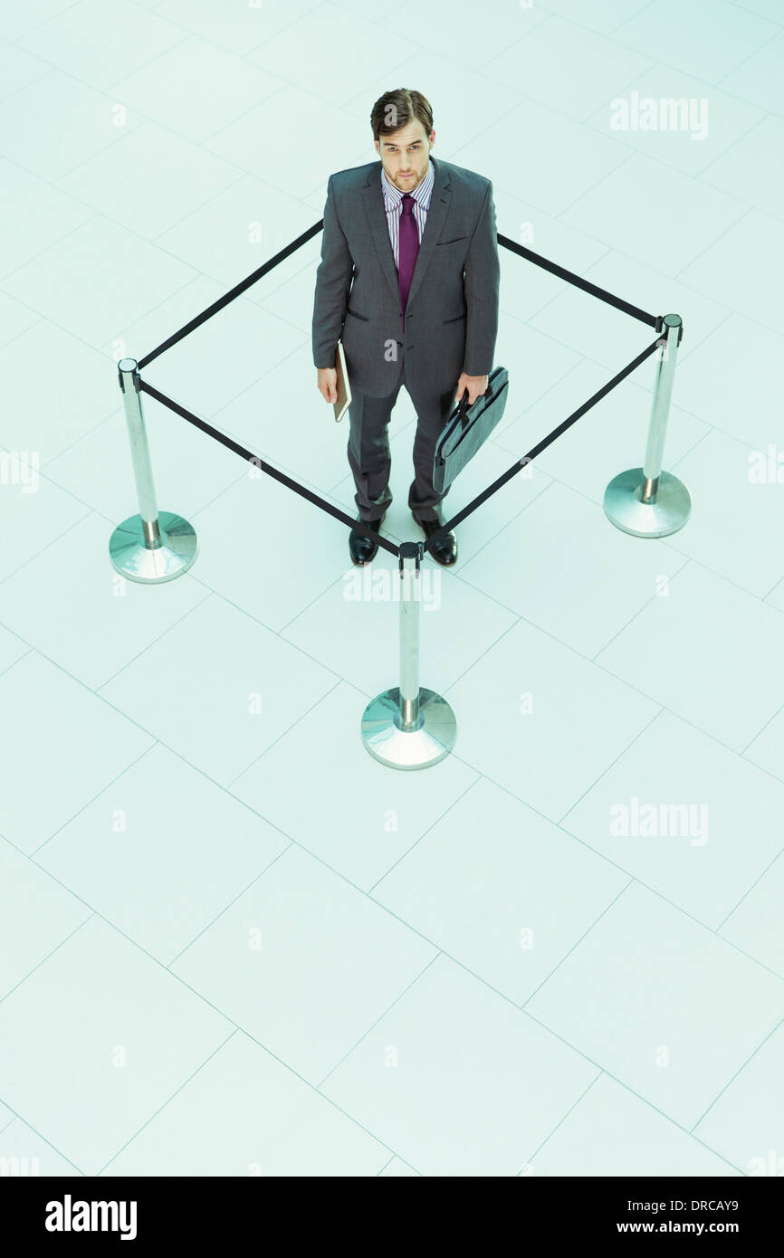 Businessman standing in roped-off square - Stock Image