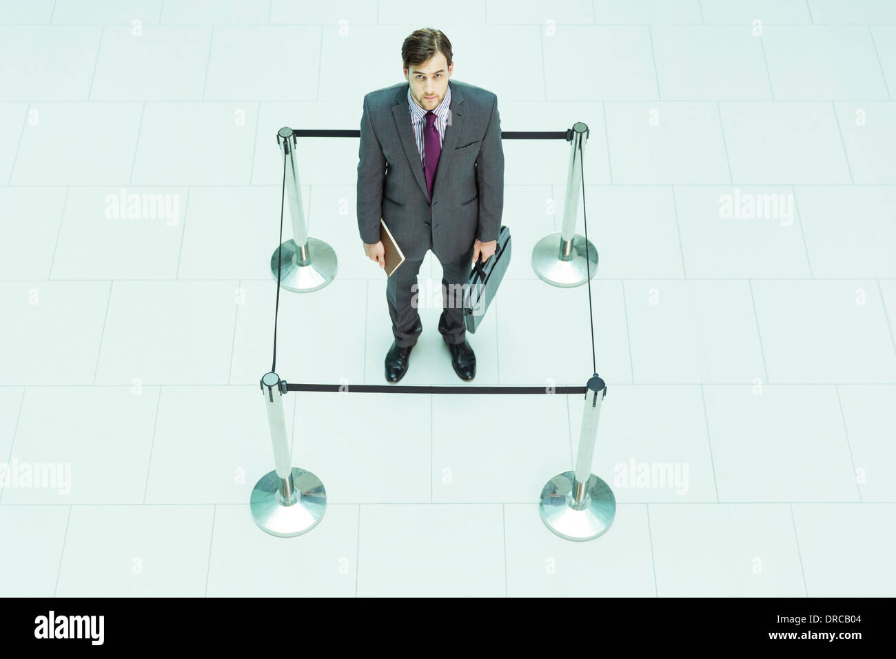 Businessman standing in roped-off square Stock Photo