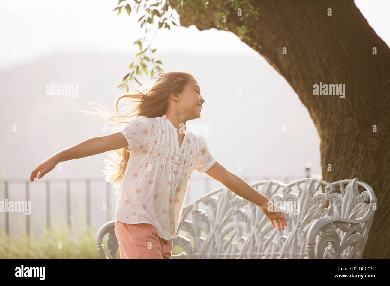 Girl running with arms outstretched - Stock Image