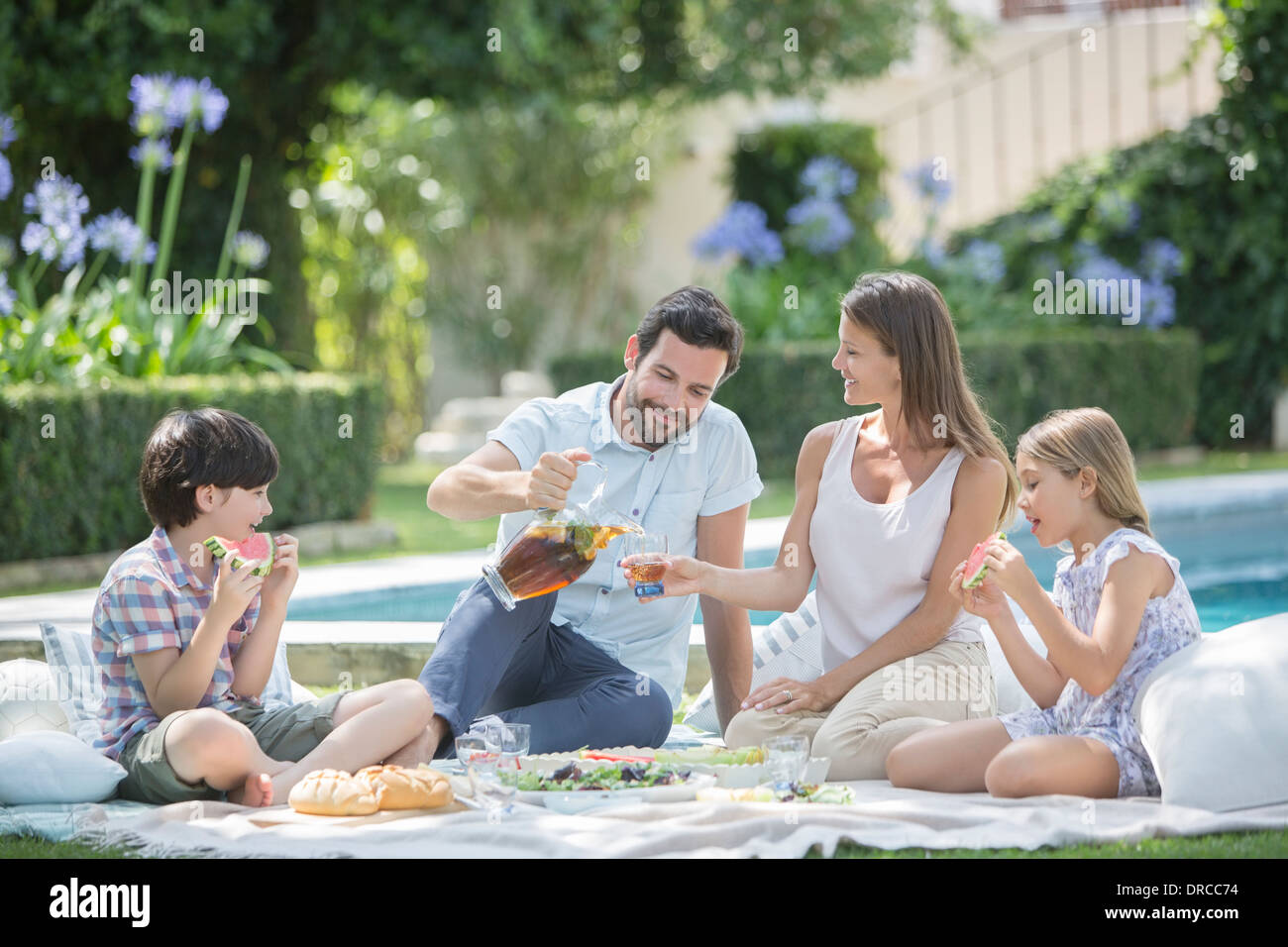 Family enjoying picnic at poolside - Stock Image