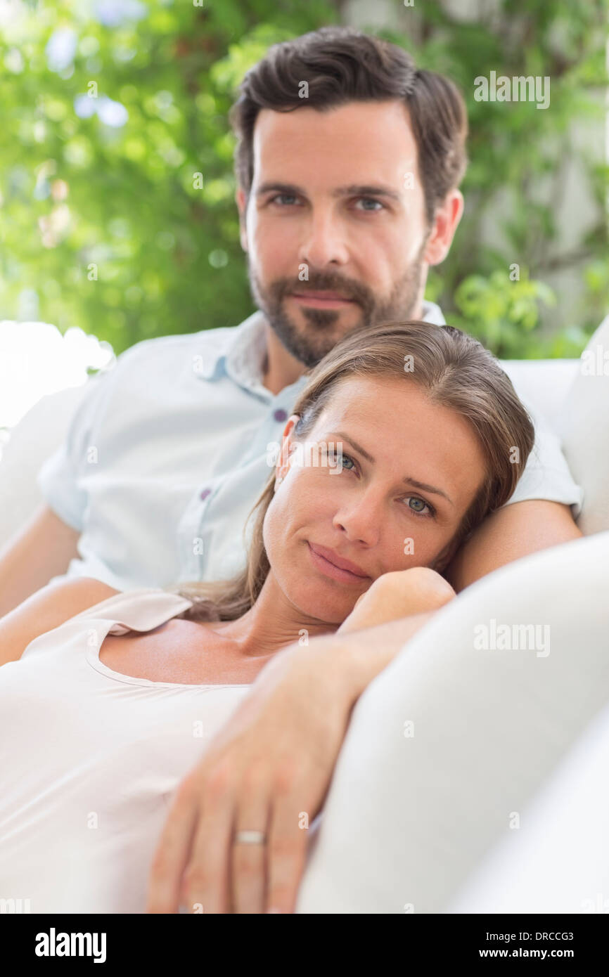 Couple relaxing on sofa outdoors - Stock Image