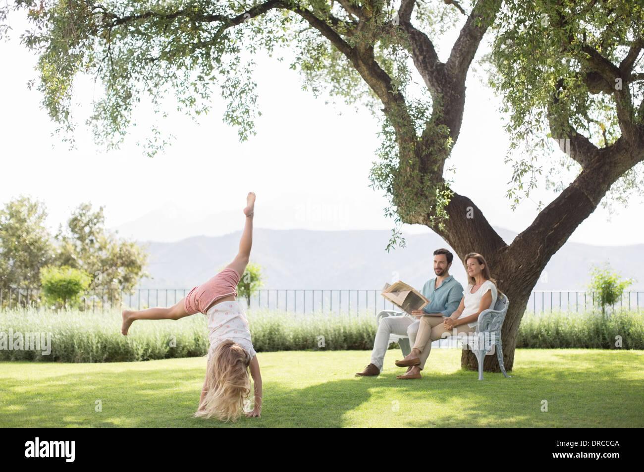 Couple watching daughter do cartwheel outdoors - Stock Image