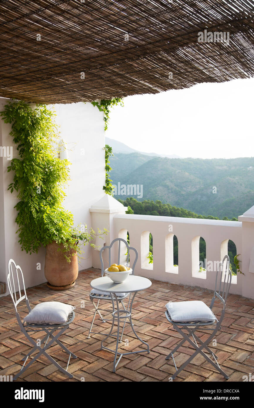 Table and chairs on balcony overlooking mountain - Stock Image