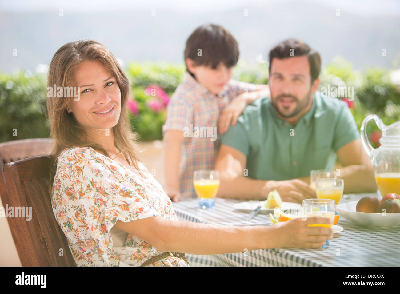 Woman smiling at patio table - Stock Image