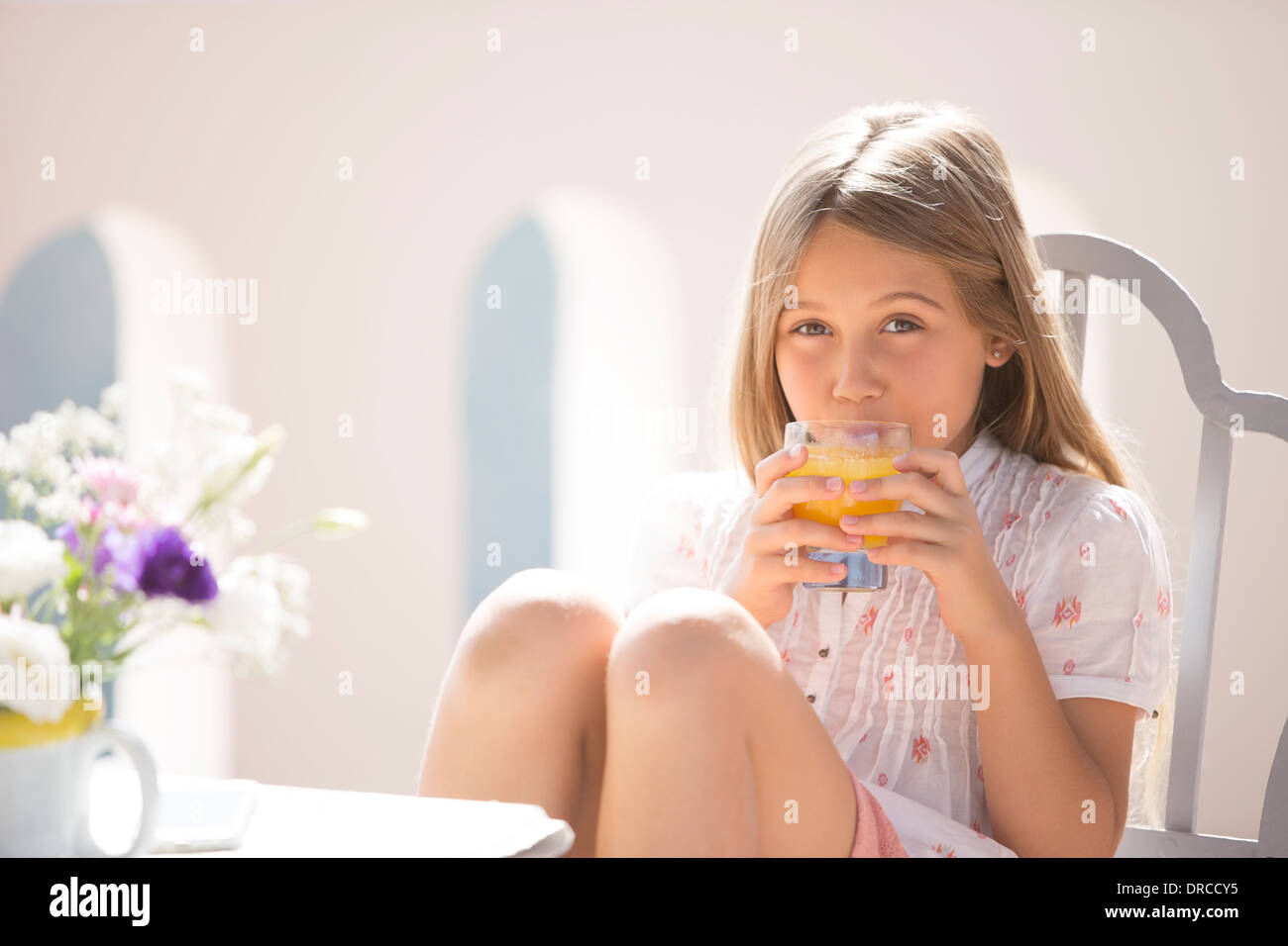 Girl drinking juice at table outdoors - Stock Image