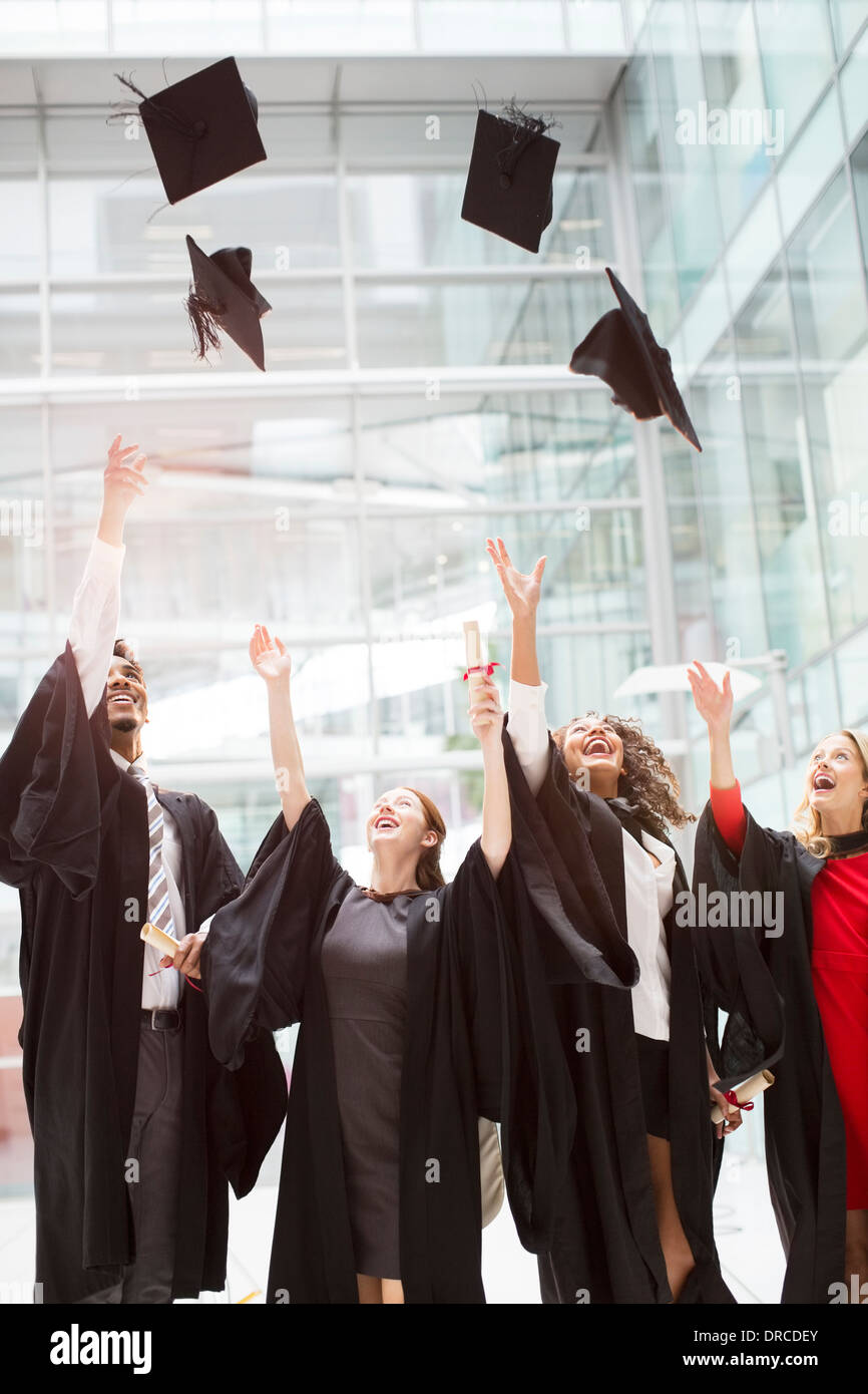 Graduates tossing caps in air - Stock Image