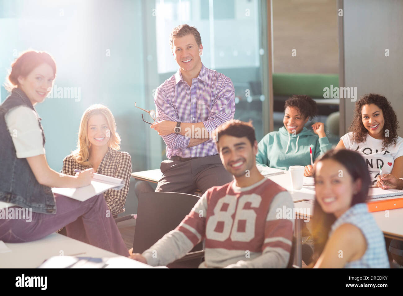 Professor and university students smiling in classroom - Stock Image