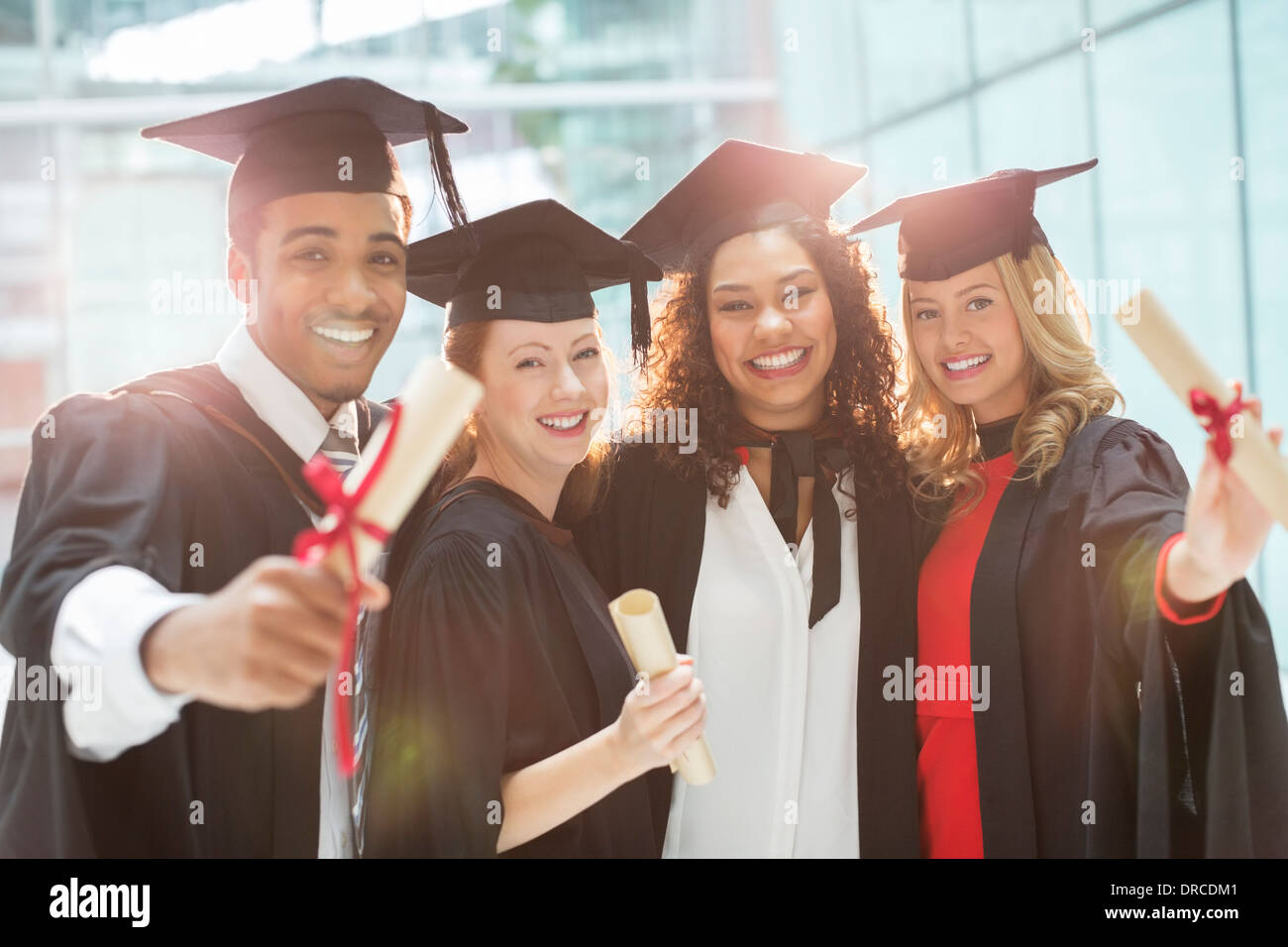 Graduates smiling with diploma - Stock Image