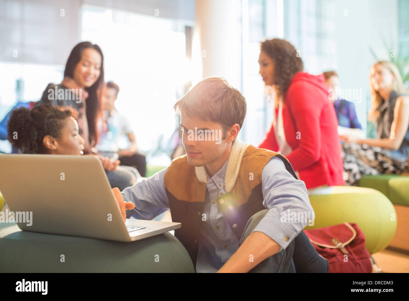 University student using laptop in lounge - Stock Image