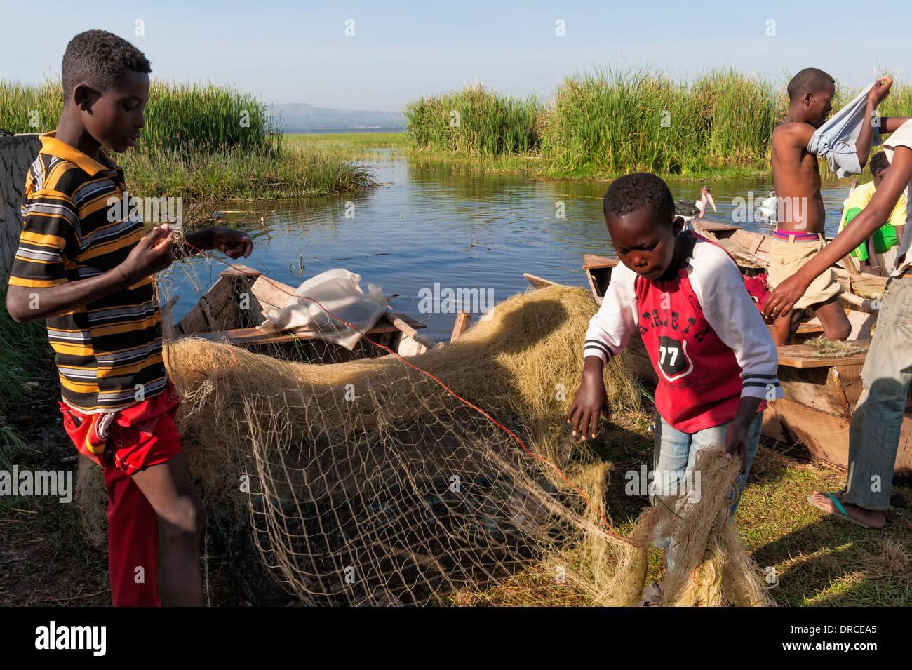Boys preparing fishing nets, Awasa, Ethiopia - Stock Image