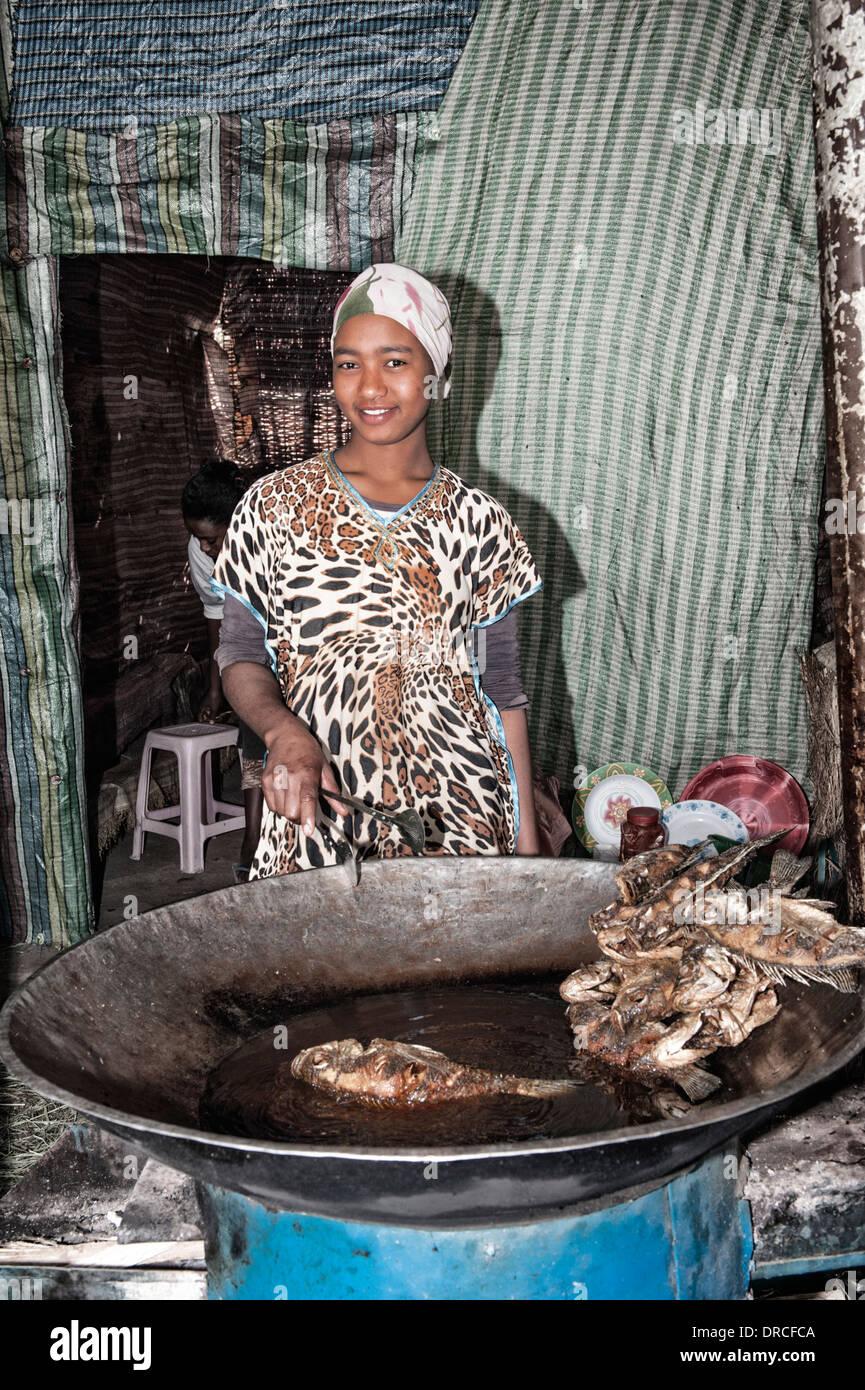 Young Woman cooking fish, Awasa harbor, Ethiopia - Stock Image