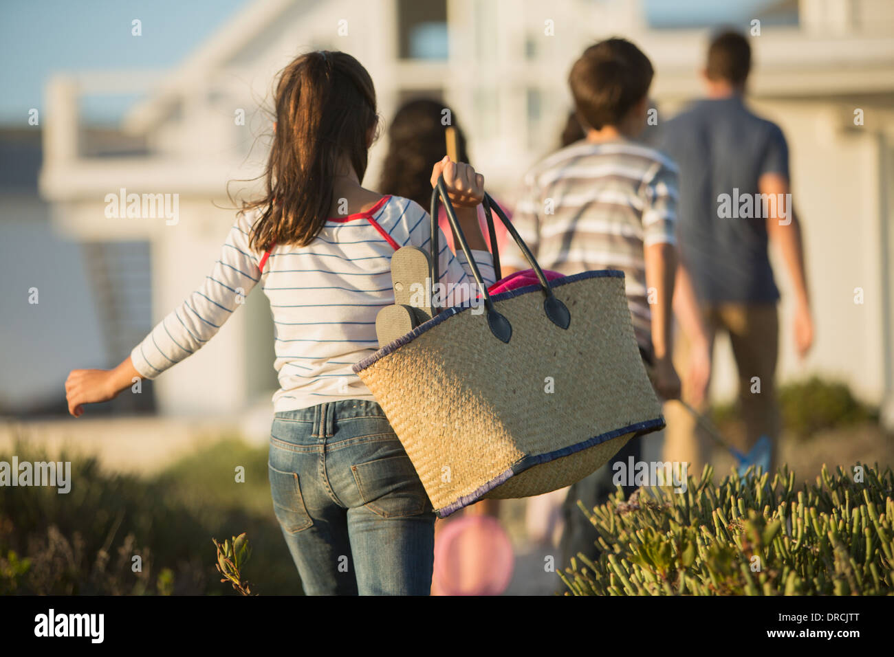 Girl with beach bag following family - Stock Image