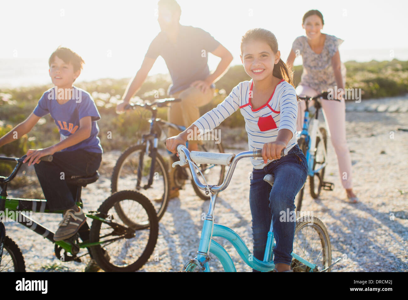 Family riding bicycles on sunny beach - Stock Image
