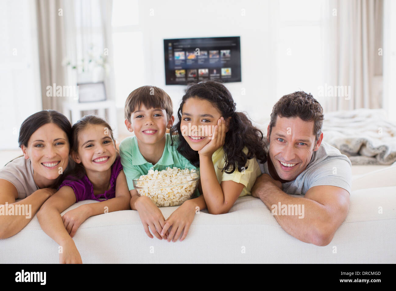 Family relaxing together on sofa in living room Stock Photo