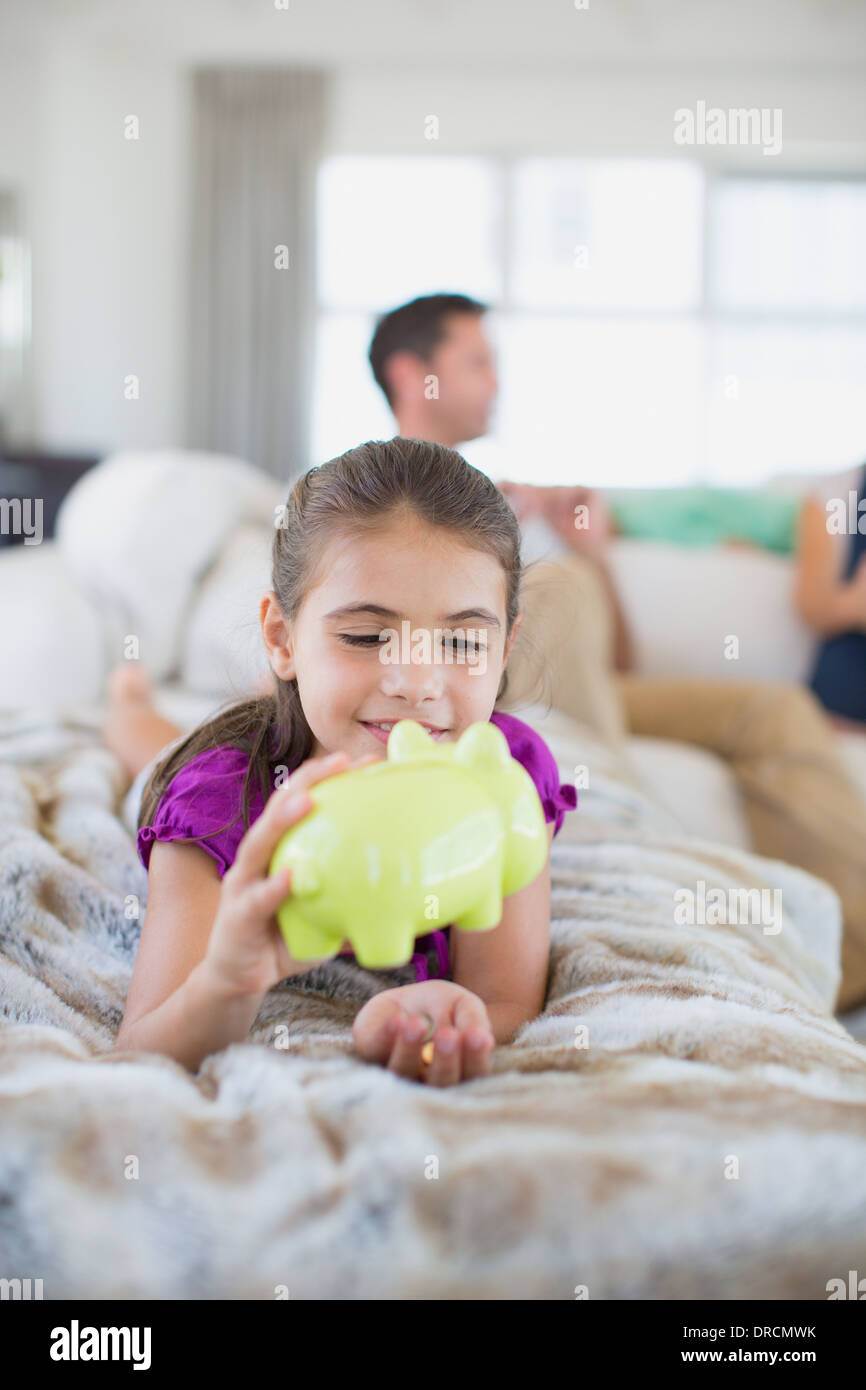 Girl counting change in piggy bank on sofa in living room - Stock Image