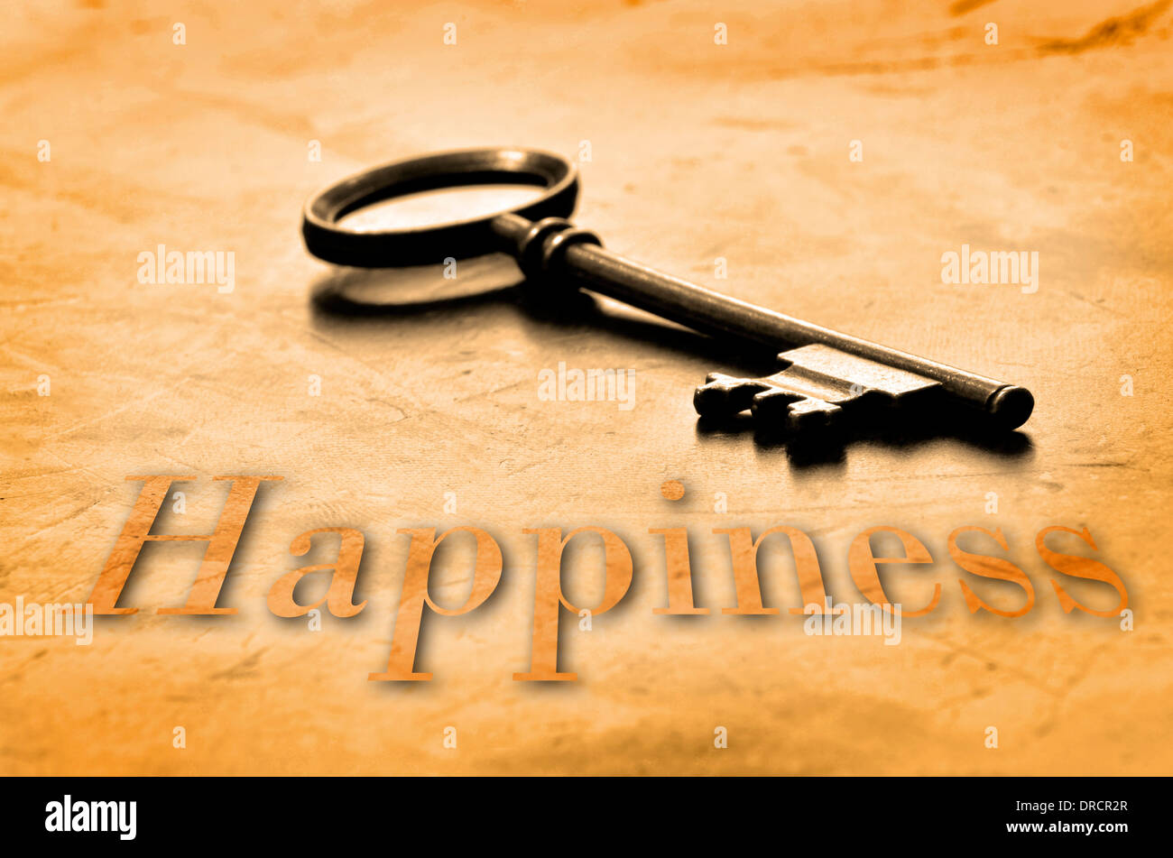 Key to Happiness on an old worn wooden desk top - Stock Image
