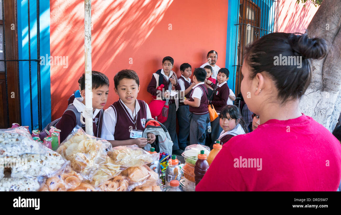 2 small Mexican schoolboys selecting after school treat from vendor's cart outside primary school General Vicente Guerrero - Stock Image