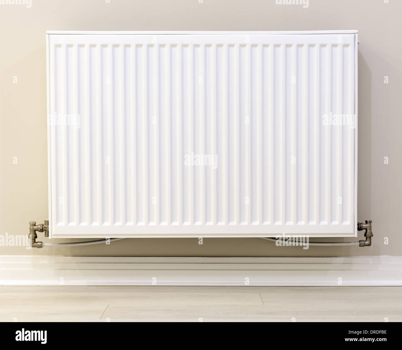 full view of a white radiator against a cream wall - Stock Image