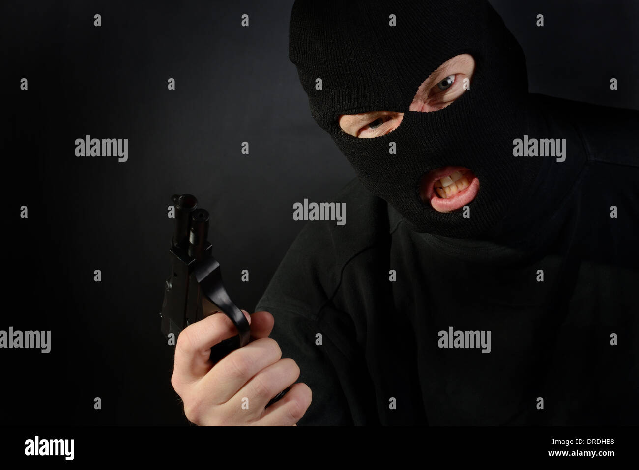 terrorist in a ski mask holding a gun with a dark background - Stock Image