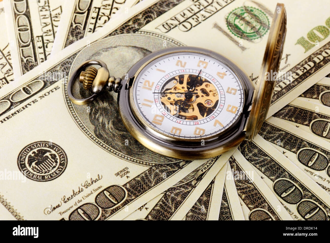 Macro shot of pocket watch face with 100 dollar bill Ben Franklin. - Stock Image