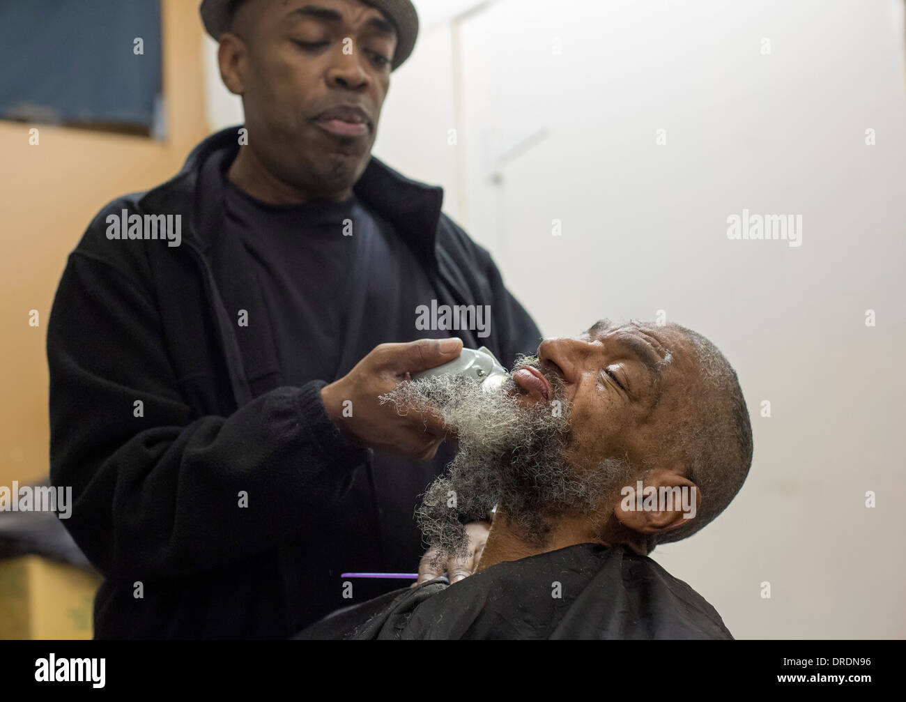 Detroit, Michigan - Barber Elvis Tucker gives a haircut and shave to a homeless man - Stock Image