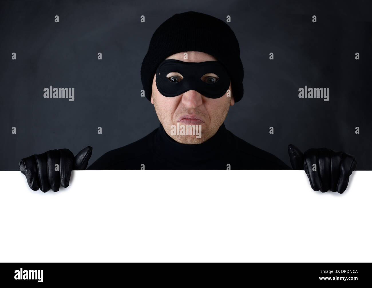 Thief peering over the top of isolated white copy space - Stock Image