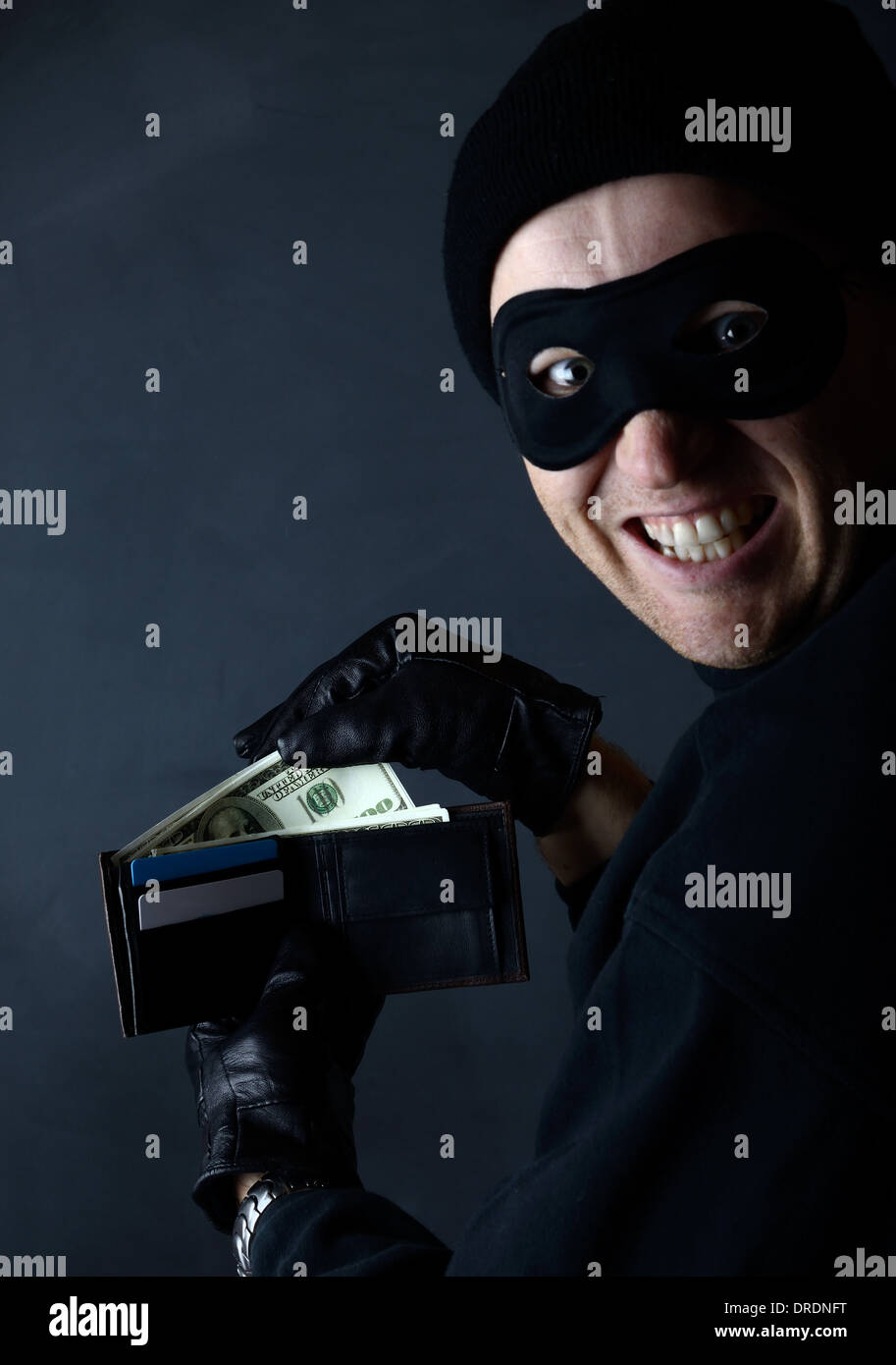A thief sealing from a wallet in a dark setting - Stock Image