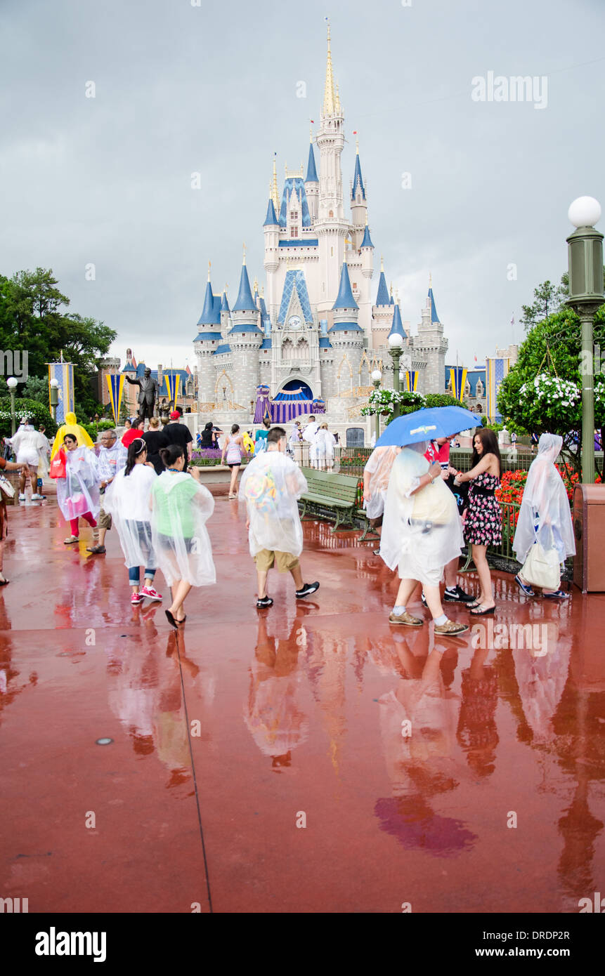 Families in Ponchos in the rain at Walt DIsney World, Orlando, Florida with the Magic Kingdom Castle in the background. - Stock Image