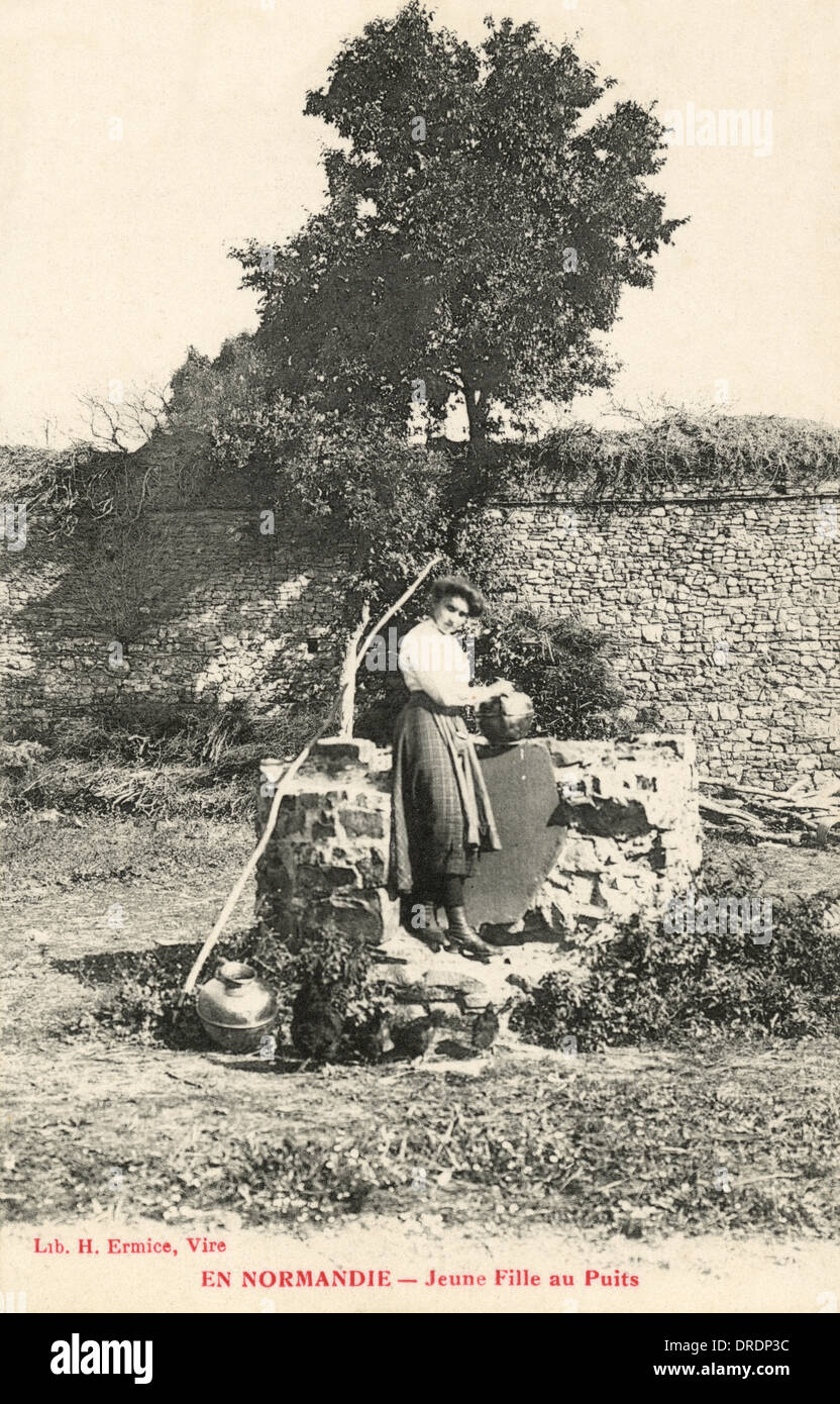 Young Woman at the well - Normandy - Stock Image