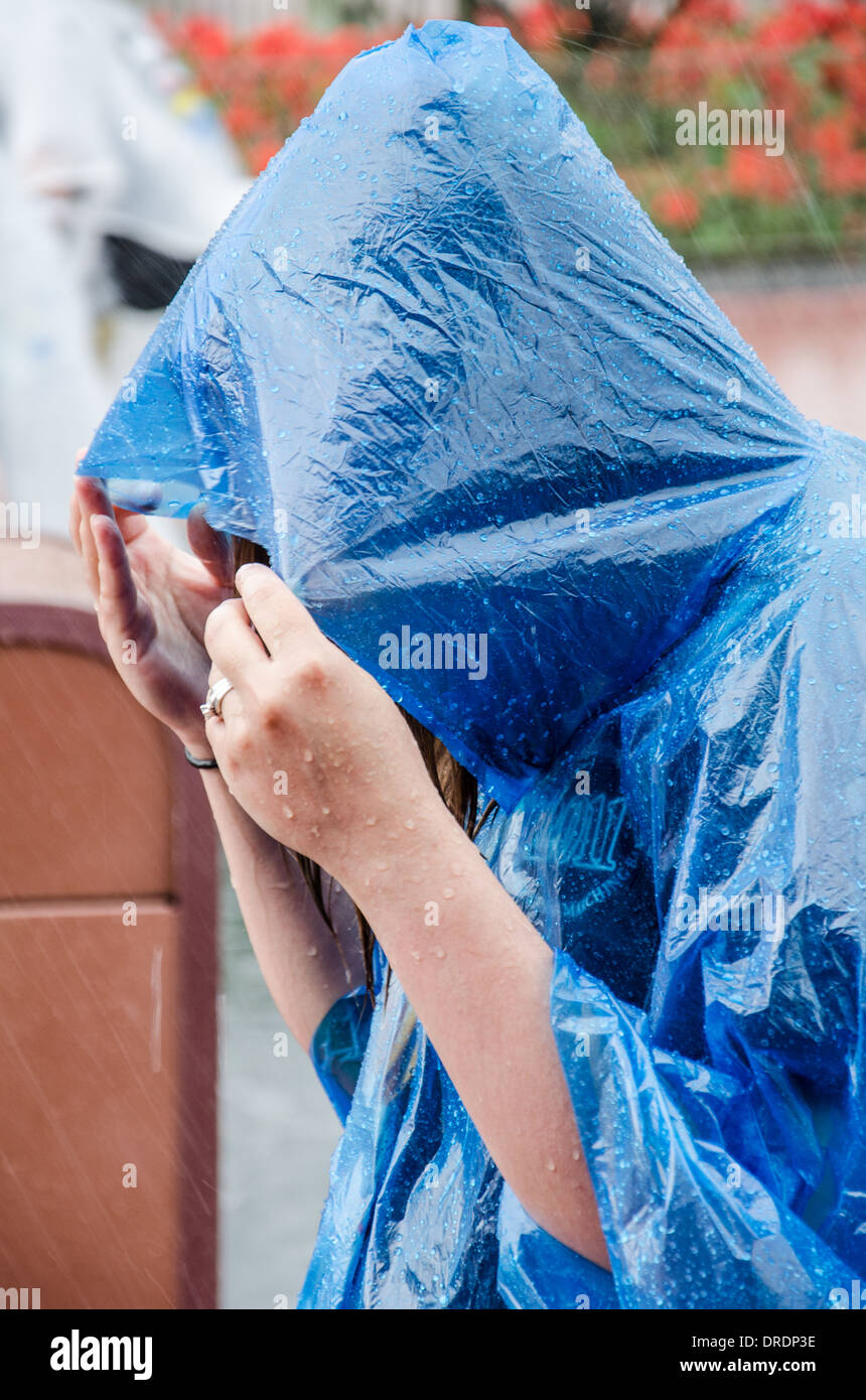 Woman sheltering from heavy rain under a blue poncho raincoat at Walt Disney World in Orlando, Florida. - Stock Image