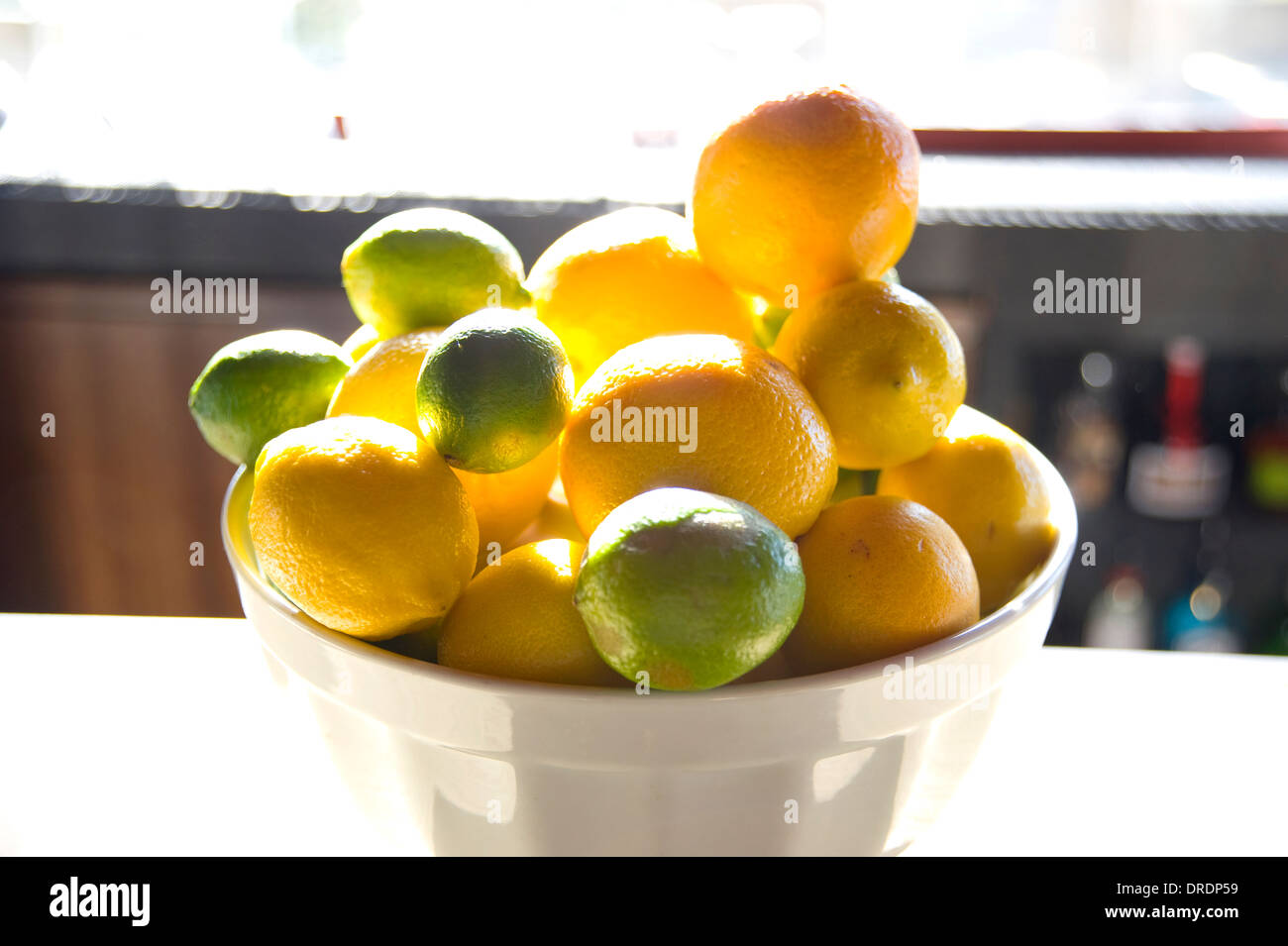 Bowl of lemons and limes on bar - Stock Image