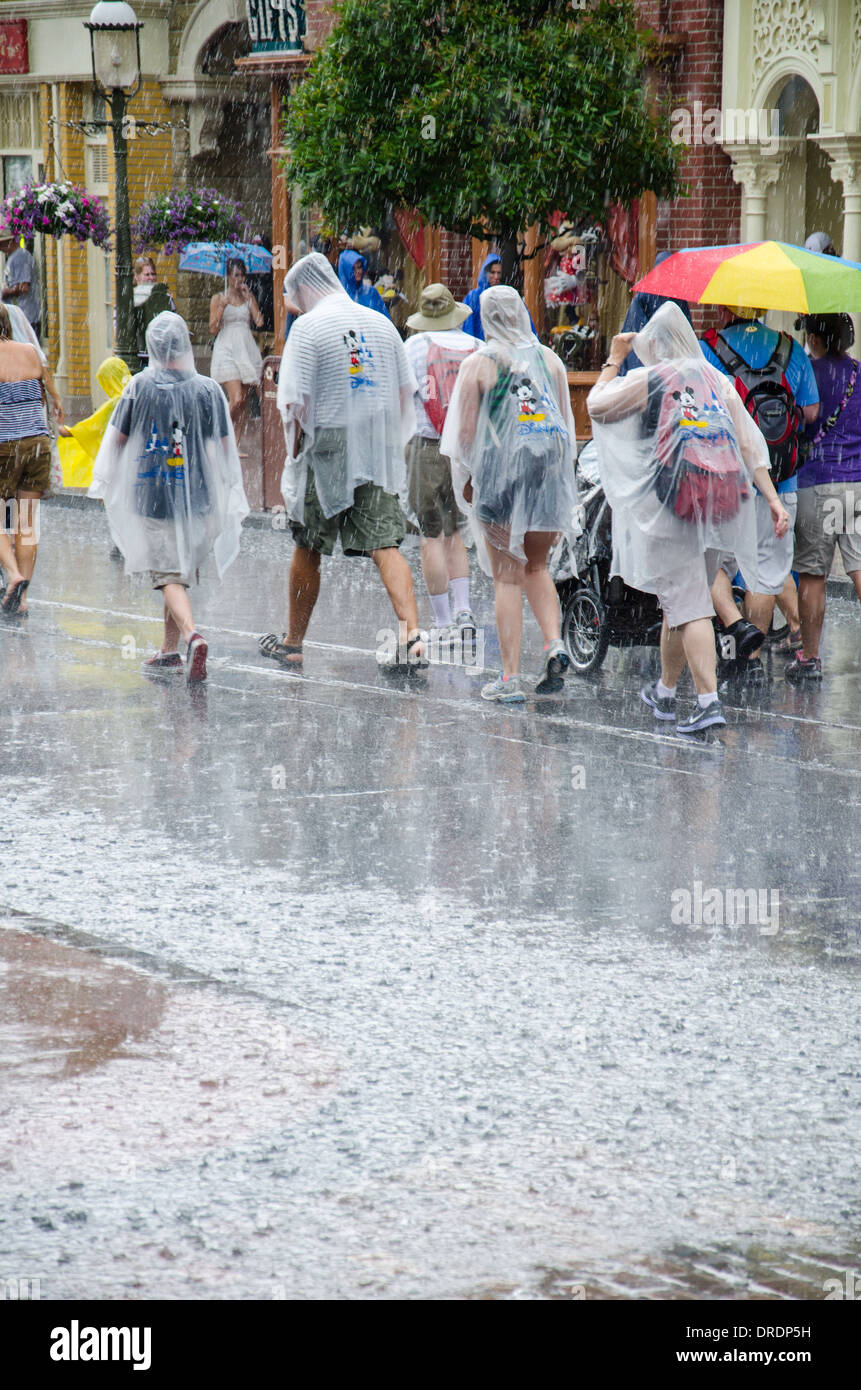 Families wearing ponchos to ward off the rain at Magic Kingdom in Walt Disney World, Orlando, Florida - Stock Image