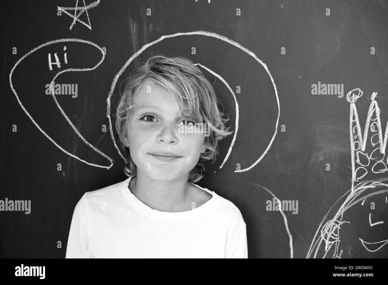 Boy standing in front of chalkboard wall, black and white - Stock Image