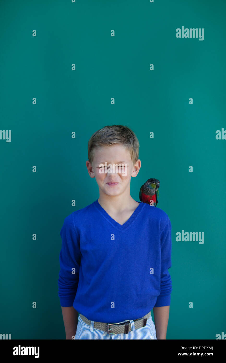 Young boy with pet parrot on shoulder - Stock Image